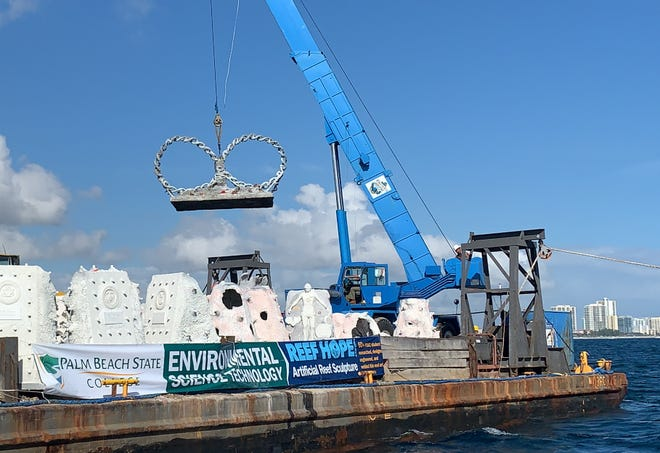 A barge gets ready to sink a stainless steel 10-ton, 11-foot-tall statue representing a DNA helix in the shape of the infinity symbol into the waters off Riviera Beach. The statue has become part of the area's artificial coral reef.