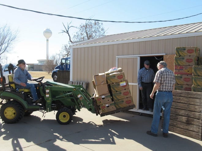 Farrell Allison, on the tractor, and Rod Hesser, watching from outside, along with Harry Koehn looking out from inside, donate labor to load donated items at the Kiowa County Care and Share store in Greensburg.