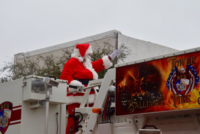Santa waves to the crowd from the bucket of the Ballinger Fire Dept's ladder truck during the Christmas in Olde Ballinger parade on Saturday.