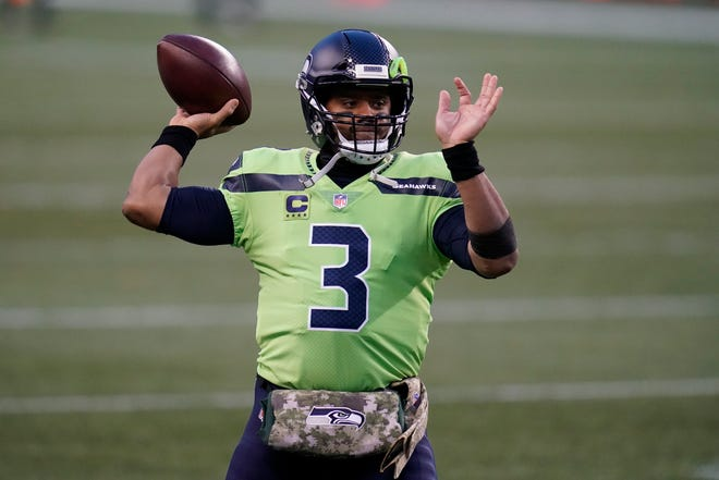 """Seattle Seahawks quarterback Russell Wilson passes during warmups before an NFL football game against the Arizona Cardinals, Thursday, Nov. 19, 2020, in Seattle. Wilson's hand-warmer is part of the NFL's """"Salute to Service"""" initiative. (AP Photo/Elaine Thompson)"""