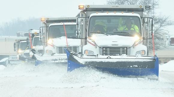Plow trucks from the Stark County Engineer's Office clear Dressler Road NW in Jackson Township during a snowstorm in this file photo.