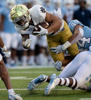 North Carolina's Jeremiah Gemmell (44) stops Notre Dame's Kyren Williams during the first quarter of an NCAA college football game Friday, Nov. 27, 2020, in Chapel Hill, N.C.