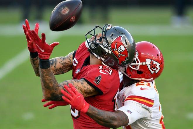 Tampa Bay Buccaneers wide receiver Mike Evans (13) can't hang onto a pass as he is held by Kansas City Chiefs cornerback Bashaud Breeland (21) Sunday, Nov. 29, 2020, in Tampa, Fla.