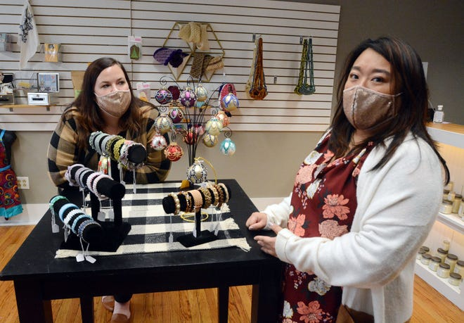 Dana Dowdell, left, and owner Molly Bruno by some hand-beaded Christmas ornaments and bracelets Monday at the newly opened Hello Home store on Franklin Street in downtown Norwich. [John Shishmanian/ NorwichBulletin.com]