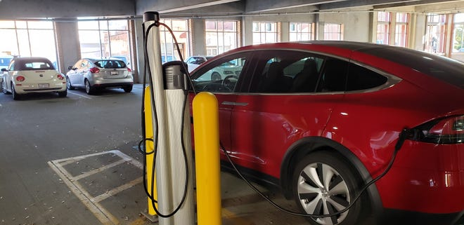 A Telsa electric vehicle charges on Saturday, November 28, 2020, at one of three EV charging stations in the parking garage on Franklin Street in downtown Fayetteville.