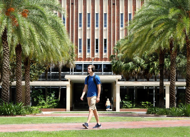 A student walks through the Plaza of the Americas past Library West on the University of Florida campus, in Gainesville Fla. Aug. 3, 2020.  [Brad McClenny/The Gainesville Sun]