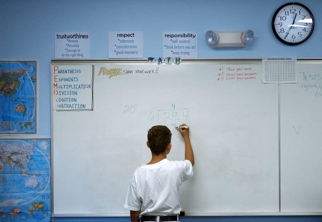 A 13-year-old boy works out a division problem during class on the Florida Sheriffs Youth Ranch in Bradenton.