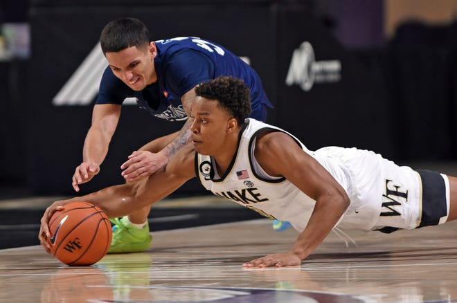 Wake Forest's Jahcobi Neath, right, and Longwood's Juan Munoz dive for a loose ball during Friday night's game.