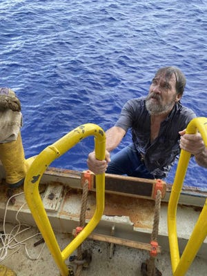 Rescued mariner Stuart Bee climbs a ladder Sunday morning after his boat sank roughly 86 miles east of Port Canaveral.