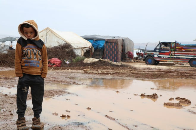 A young boy stands alone in the camp during winter. Temperatures in Syria can often dip below freezing in the winter months, but Syrian Forum provides winter gear and heaters to those in need.