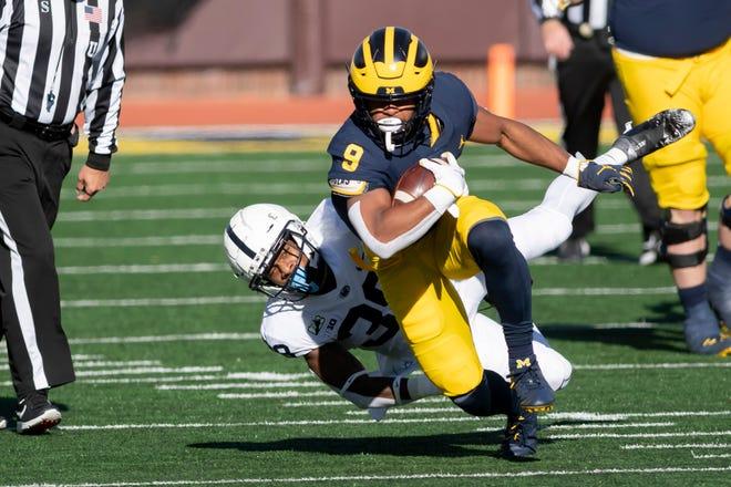 Michigan berlari kembali Chris Evans ditangani oleh keamanan Penn State Lamont Wade pada kuarter kedua Sabtu di Ann Arbor.