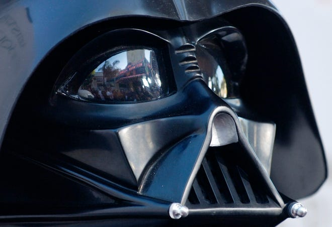 """FILE - In this file photo dated Thursday, May 12, 2005, the Los Angeles, USA, premiere of the movie """"Star Wars: Revenge of the Sith"""",  is reflected in the mask eyeglasses of iconic baddie character Darth Vader.  The British actor, Prowse who played Darth Vader in the original Star Wars trilogy, has died aged 85 on Saturday, according to an announcement by his agent Sunday Nov. 29, 2020. (AP Photo/Chris Pizzello, FILE)"""