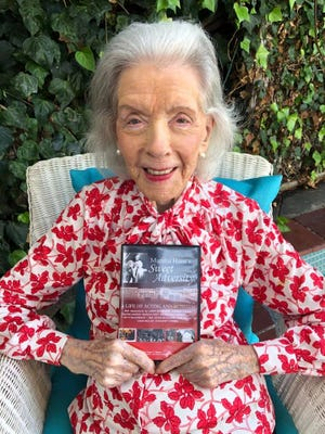 Marsha Hunt holds a DVD copy of the documentary on her 103rd birthday.