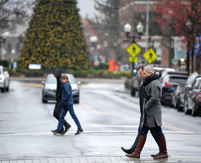 People walk in downtown Franklin as snow and sleet falls Monday morning, Nov 30, 2020.