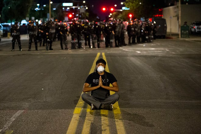 Protester DeRon Stanton meditates near police officers in riot gear in downtown Phoenix on May 30, 2020, to honor the life of George Floyd, 46, who died under the knee of a Minneapolis police officer on Monday.