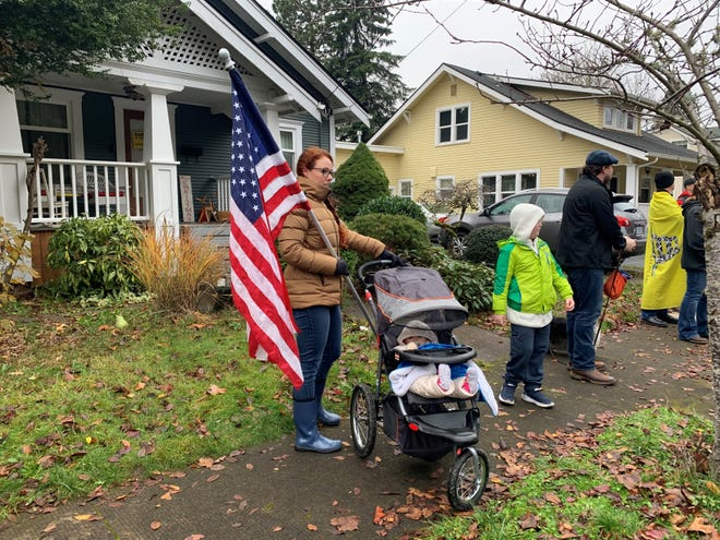Mary Beth Wilson, of Vancouver, Washington, and her children ages 1 and 8, join more than 100 people in a Silverton, Oregon neighborhood on Sunday, Nov. 29, 2020 to protest the $90,000 fine slapped on Salem's Courthouse Club Fitness for defying Gov. Kate Brown's COVID-19 closure order.