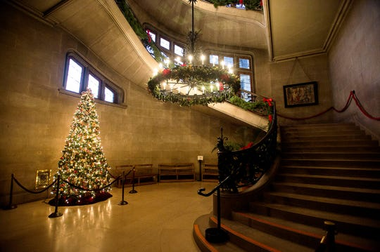 A bright and beautifully decorated Christmas tree lights the stairwell by the entrance to the Biltmore House.