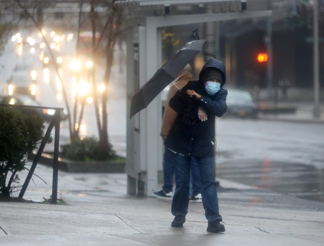 A pedestrian struggles with his umbrella as he walks amid wind and rain in downtown White Plains Nov 30, 2020.
