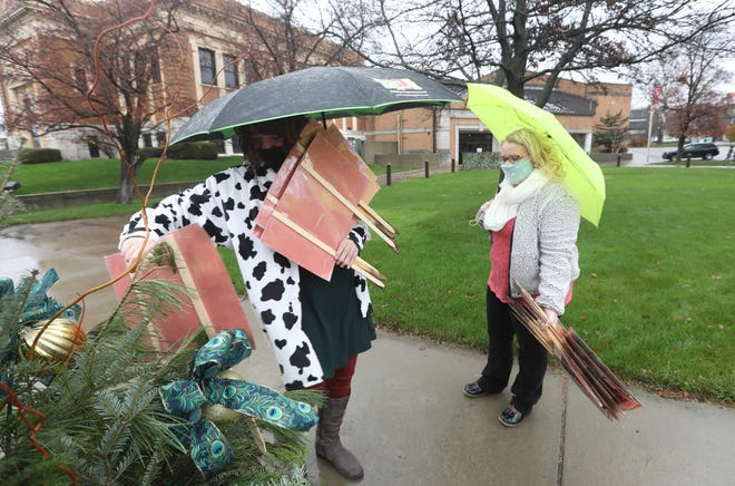 Katie Merritt, right, and Alyssa Fisher brave the elements to set up the Muskinugum County Library System's December Story Walk on Monday. 17 story boards set up around downtown Zanesville tell the story of Snowmen at Work by Caroline Buehner.