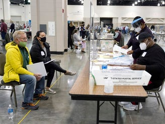 FILE - Election workers, right, verify ballots as recount observers, left, watch during a Milwaukee hand recount of presidential votes at the Wisconsin Center, Friday, Nov. 20, 2020, in Milwaukee. Wisconsin finished a partial recount of its presidential results on Sunday, Nov. 29, 2020 confirming Democrat Joe Biden's victory over President Donald Trump in the key battleground state. Trump vowed to challenge the outcome in court. (AP Photo/Nam Y. Huh) ORG XMIT: NYPS210