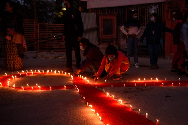 Volunteers light candles forming the shape of a red ribbon during an awareness event on the eve of the World AIDS Day, in Kathmandu on November 30, 2020.