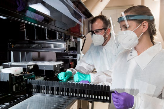 In this Wednesday, July 22, 2020, photo provided by C2N Diagnostics, Matthew Meyer, left, senior proteomics scientist, and Stephanie Knapik, a research associate, work in a lab that analyzes blood samples at the company's facility in the Center for Emerging Technologies in St. Louis. C2N Diagnostics has started selling the first blood test to help diagnose Alzheimer's disease, a leap for the field that could make it much easier for people to learn whether they have dementia. It also raises concern about the accuracy and impact of such life-altering news.