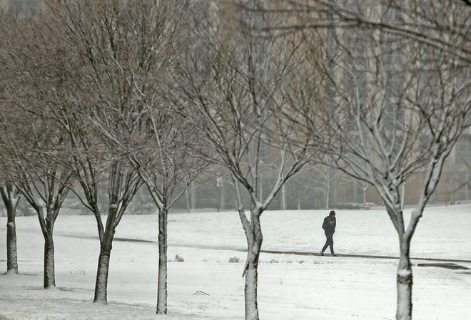 A Kent State student walks to class during a snowstorm, Tuesday, Dec. 1, 2020, in Kent, Ohio. [Jeff Lange/Beacon Journal file photo]