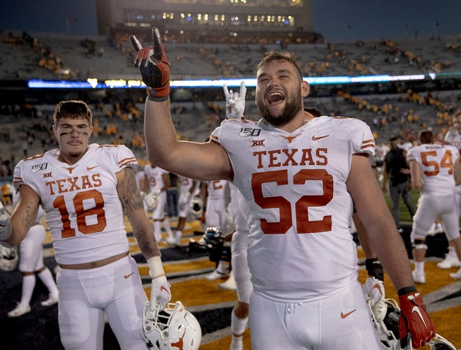 "Texas offensive lineman Samuel Cosmi (52) holds up the ""Hook 'Em Horns"" gesture after Texas defeated West Virginia 42-31 in an NCAA football game on Saturday, Oct. 5, 2019, in Morgantown, W. Va. [NICK WAGNER/AMERICAN-STATESMAN]"