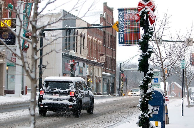 Traffic travels down West Main Street in Ashland past the Christmas decorations that were put up Monday. By Tuesday morning, they were covered with snow.