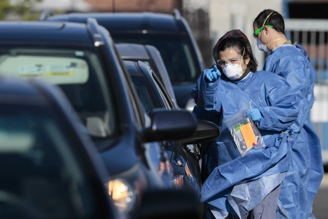 A medic directs a driver at a drive-thru COVID-19 testing site at PrimaryOne Health in Columbus.