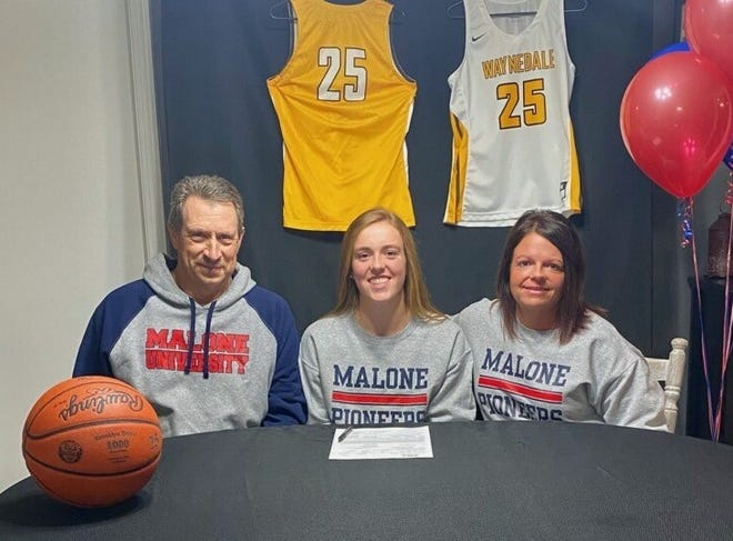 Waynedale's Brooklyn Troyer, accompanied by parents Ray (left) and Angie (right), celebrates signing to play college basketball at Malone University.