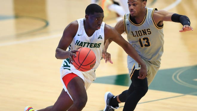 Stetson's Rob Perry, left, drives toward the basket against Emmanuel College's Kendall Latney. Perry scored a game-high 26 points but it wasn't enough as the Hatters lost their men's basketball opener to the Lions, 64-61, on Monday, Nov. 30, 2020 at the Edmunds Center in DeLand.