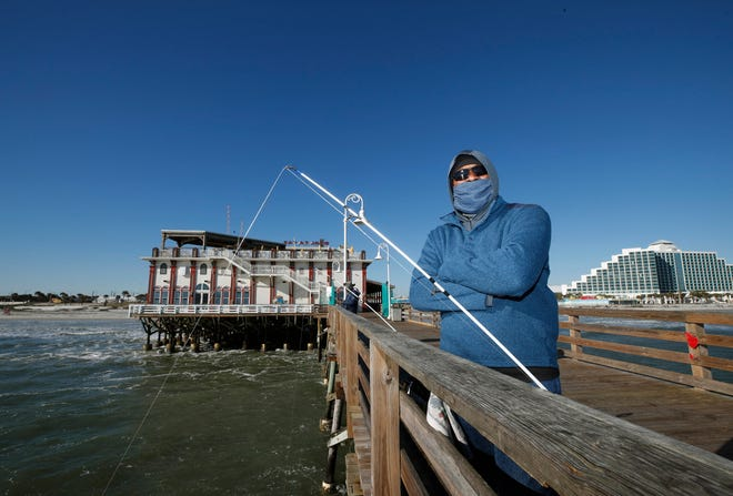Larry Jones watches his fishing line while braving the cooler temps to fish from the Daytona Pier in Daytona Beach on Tuesday, Dec. 1, 2020.