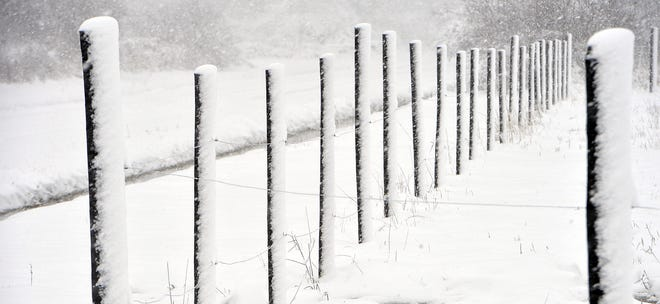Snow falls on fencing Tuesday near the intersection of West and Babbitt in Elk Creek Township.
