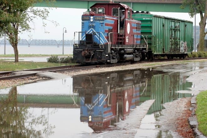 In this file photo, a Burlington Junction Railway train is reflected in the rain-filled road along the Mississippi River in Burlington. BJR will movea portion of its track from north of and next to the Burlington Memorial Auditorium toan area just north of Bluff Harbor Marina.