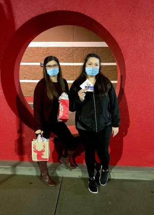 Sisters Alexis, left, and Jayde Hassen pose while hiding presents at Target over Thanksgiving weekend as part of their Strafford County Secret Santa game. Thousands of people are participating in the game in Strafford County and in Maine's York County, hiding presents in public places and posting photos and hints on the game's Facebook pages so others can find them.
