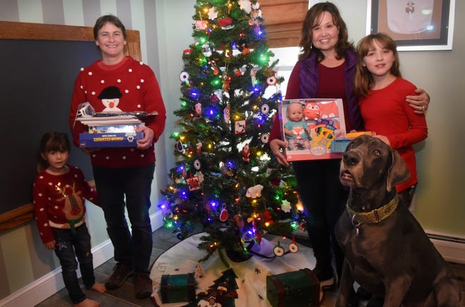 Former Rollinsford fire captain Jaimie Adams, left, and her daughter, Teagen, along with, on the right, Jenn Lavoie and her daughter, Charlotte O'Rourke, hope to inspire others to give to the Rollinsford Holiday Toy Drive this year. Also in the photo is Great Dane Baxter.