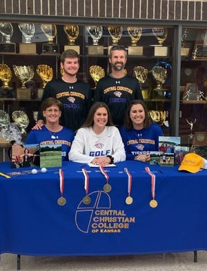 Shallowater senior Kami Wood (center) is surrounded by family members after signing her national letter of intent to play golf at Central Christian College on Tuesday at Shallowater High School.