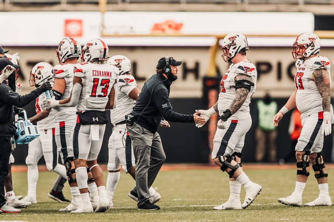 Texas Tech graduate assistant coach John Cannova, center, greets offensive guard Jack Anderson during the Red Raiders' 50-44 loss Saturday at Oklahoma State. Cannova took on a more important role with offensive line coach Steve Farmer unavailable for the game.