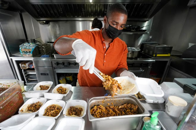 Chef Akino West makes chicken tacos during a food distribution event by Food Rescue US on Monday in the Overtown neighborhood of Miami. On Tuesday, Florida reported 8,847 new cases to push the state's total to 1,008,166. The death toll rose by 82 to 18,916.