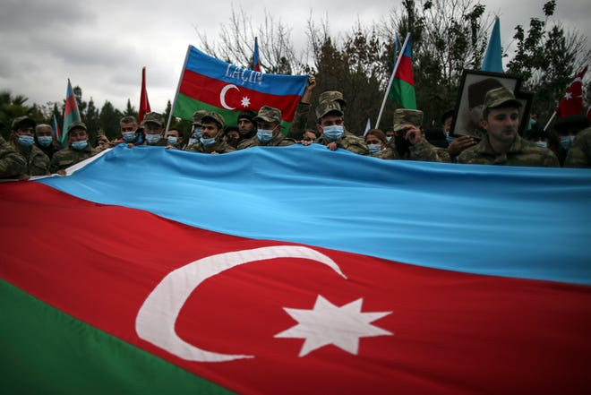 Azerbaijani soldiers hold a huge national flag Tuesday as they celebrate the transfer of the Lachin region to Azerbaijan's control, as part of a peace deal that required Armenian forces to cede the Azerbaijani territories they held outside Nagorno-Karabakh, in Aghjabadi, Azerbaijan.