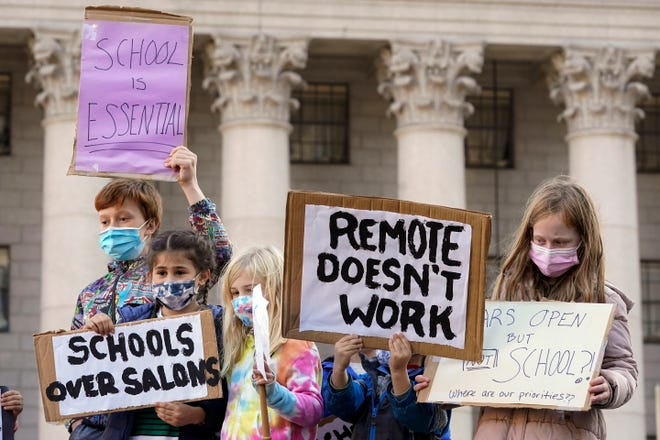 Students demonstrate during a rally last month to call on New York Mayor Bill de Blasio to keep schools open. Classroom doors will open for elementary school students next week, but middle school and high school students in New York City won't return to in-person learning until after the holiday break, De Blasio said Monday.