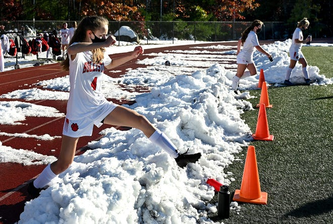 Holliston's Mia Wolfgang jumps over a snowbank in between quarters during a game against Medway at Medway High School on Oct. 31.