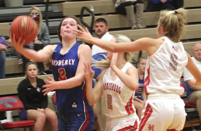 Moberly freshman Grace Billington gets around Harrisburg's Charlea Winscott and Baylie Combs (#5) to release a shot Monday during a non-league varsity girls basketball game played on the Bulldogs' home floor. Billington scored a game-high 27 points to guide Moberly to a 63-57 victory.