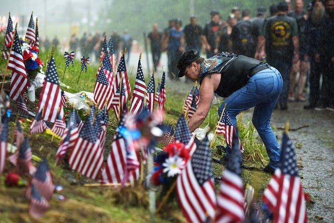 In this July 6, 2019, file photo, a woman views the memorial site for seven bikers who were killed in a collision while riding with the Jarheads Motorcycle Club June 2019, in Randolph, N.H. The National Transportation Safety Board found Tuesday, Dec. 1, 2020, a pickup driver's drug use was the reason he crashed last year into the oncoming group of motorcyclists in New Hampshire, leading to the death of the bikers.  [Paul Hayes/Caledonian-Record via AP, File]