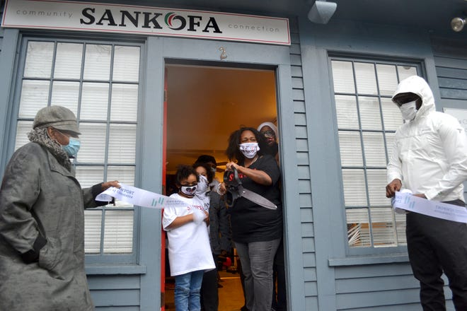 Niko Merritt, founding executive director of Sankofa Community Connection, cuts the ribbon to the organization's new Broadway location in a ceremony Monday.