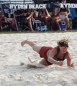 Ainsley dives for the ball while playing beach volleyball.