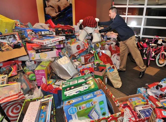 John McKinley places a stuffed bear on top of a pile of donated toys during the 9th annual Braintree Christmas Party in 2018.