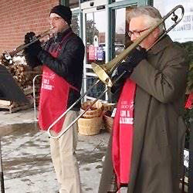 Harlan Geiser, right, and his son, Chad, play music outside of a Bloomington store during a previous holiday season.