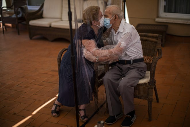Agustina Canamero, 81, and Pascual Perez, 84, hug and kiss through a plastic film screen to avoid contracting the coronavirus at a nursing home in Barcelona, Spain, in June. EMILIO MORENATTI / ASSOCIATED PRESS